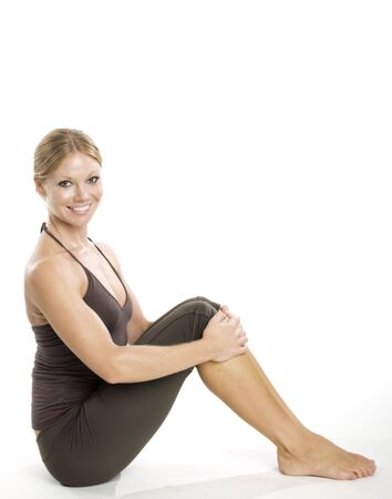 An attractive young woman with a smile stretching.
