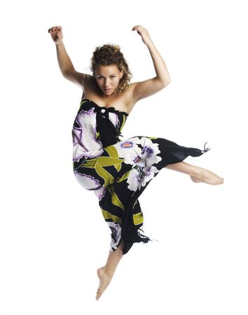 A young attractive  blond Caucasian woman in a facy dress dancing in the air on white background. Stok Fotoğraf