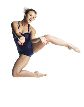 A young attractive  blond Caucasian woman in blue leotard dancing in the air on white background.