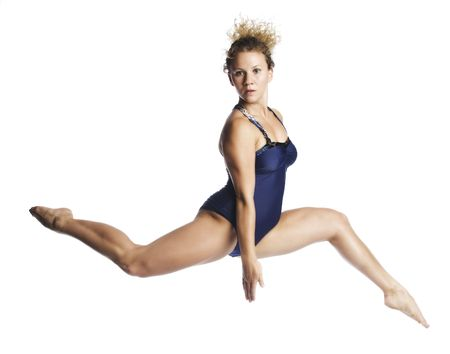 A young attractive  blond Caucasian woman in blue leotard dancing in the air on white background. photo