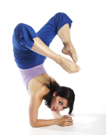 A young attractive Asian woman in lavender top and blue sweatpants doing yoga on white background.