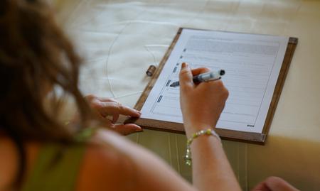 Novia caucásica firma para matrimonio en la oficina de registro civil