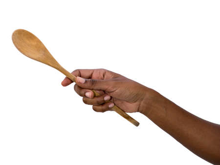 Hand holding wooden spoon