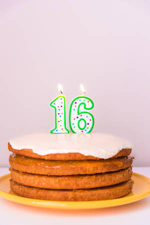 Sixteenth birthday candles on rustic vegan layered cake pastel background