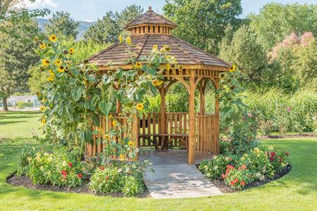 Garden gazebo in public city park with sunflowers and dahlias Stock Photo