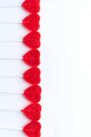 Heart shaped red valentine lollipops in row along left side with white background