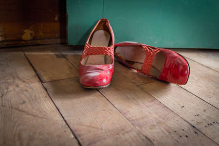 Worn red womens dress shoes on wooden floor