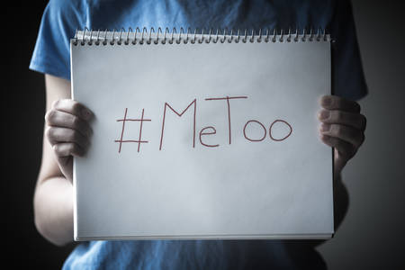 Young woman standing in shadow holding  notepad into the light with #MeToo written on the  page