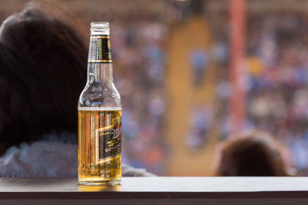 Williams Lake, British ColumbiaCanada - July 2, 2016: bottle of beer rests on a ledge in the VIP stands with audience in the background, at the internationally famous 90th Williams Lake Stampede Redakční