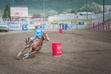 Williams Lake, British Columbia/Canada - June 30, 2016: a barrel racer swerves around the second barrel at the 90th Williams Lake Stampede, one of the largest stampedes in North America