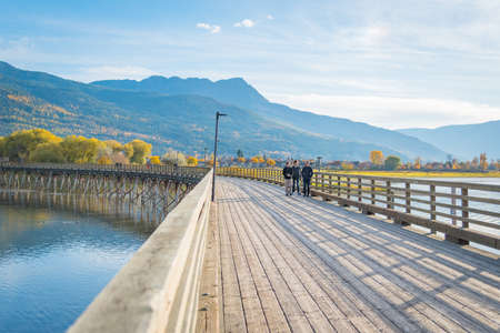 Salmon Arm, British Columbia/Canada - October 22, 2016: families take an evening walk along the longest curved pier in North America, located at the Salmon Arm Wharf on Shuswap Lake.