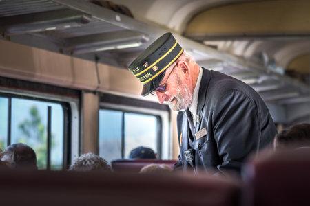 Summerland, British Columbia / Canada - 14 mei 2017: de dirigent neemt kaartjes van passagiers op de Kettle Valley Steam Railway, een populaire toeristische attractie in Okanagan.