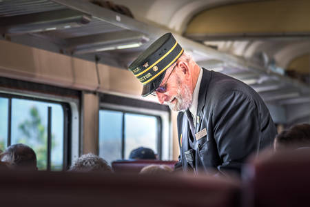 Summerland, British Columbia/Canada - May 14, 2017: the conductor takes tickets from passengers on the Kettle Valley Steam Railway, a popular tourist attraction in the Okanagan. 新闻类图片