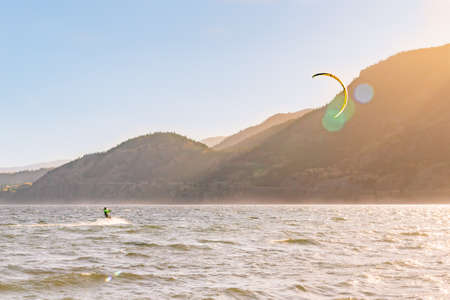 PENTICTON, BRITISH COLUMBIA, CANADA - OCTOBER 24, 2017 a kiteboarder enjoys sailing across Skaha Lake near Sudbury Beach on a windy autumn evening. This area is a very popular location for the sport