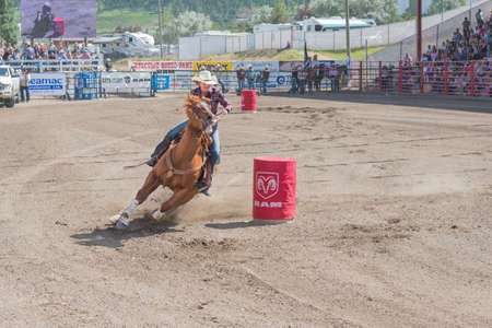 Williams Lake, British Columbia/Canada - July 2, 2016: horse and cowgirl take a tight turn around a barrel at the 90th Williams Lake Stampede, one of the largest stampedes in North America