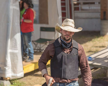 Williams Lake, British ColumbiaCanada - July 2, 2016: cowboy walks toward arena to compete in the Wild Horse Race at the 90th Williams Lake Stampede, one of the largest stampedes in  North America