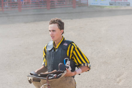 Williams Lake, British ColumbiaCanada - July 2, 2016:  a teammate at the Wild Horse Race stands ready with a saddle while his team tries to catch the horse, during the 90th Williams Lake Stampede