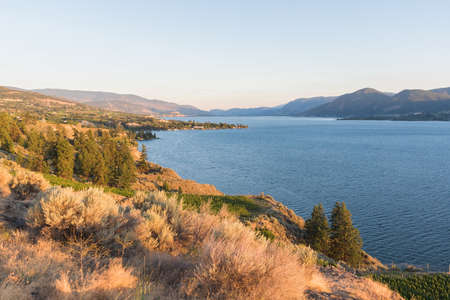 View of the Naramata Bench, Okanagan Lake, and mountains looking south toward Penticton at sunset Stock Photo