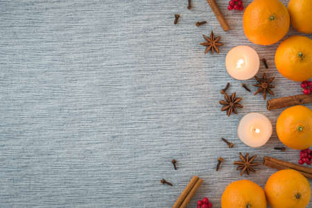 Flat lay seasonal arrangement of oranges, spices, and candles