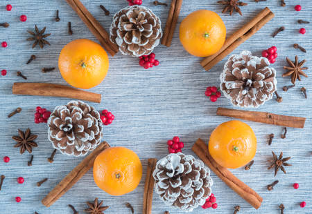Holiday wreath arrangement of oranges, pinecones, spices, and red berries