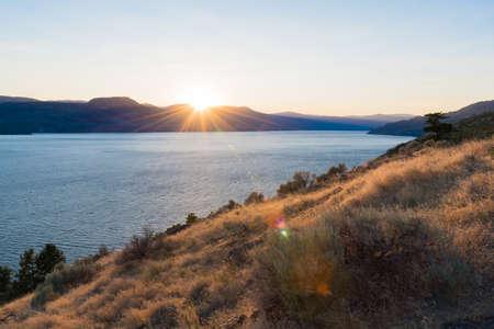 Sun setting behind the mountains over Okanagan Lake in summer Stok Fotoğraf