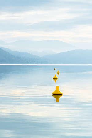 Yellow buoys on calm lake reflecting sky and mountains 版權商用圖片