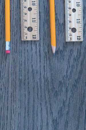 Pencils and rulers on gray wood grain background flat lay arrangement