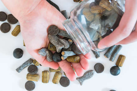 Assorted double salted liquorice being poured from candy jar into womans hand Stok Fotoğraf