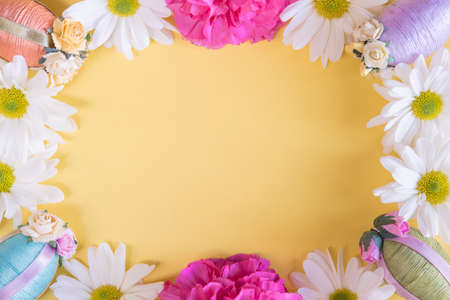 Flat lay frame of Easter eggs and flowers on solid pastel yellow background