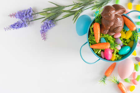 Flat lay Easter background with mini carrots, lavender, Easter eggs, and chocolate bunny
