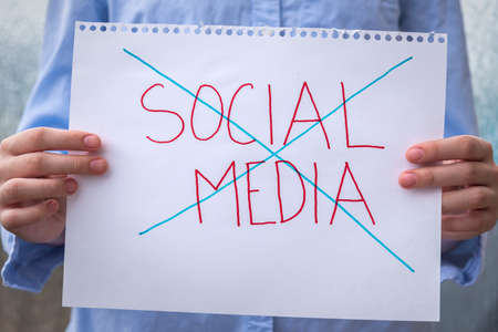 Close-up of sign held in front of person with the words social media crossed out to illustrate the growing trend of deleting social media accounts