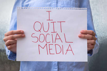 Close-up of person holding sign in front of chest that says I Quit Social Media