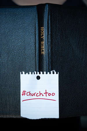 Close-up of Holy Bible with #churchtoo hashtag on cover, representing the cover-up of sexual abuse in churches