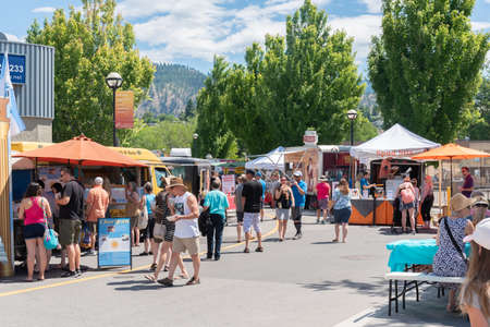 Penticton, British ColumbiaCanada - June 15, 2019: crowds enjoy the various food trucks at the Penticton Community Market, a popular weekly event for tourists and locals.