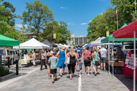Penticton, British ColumbiaCanada - June 15, 2019: people shop for local foods at the Penticton Farmers Market, a popular market for tourists and locals.