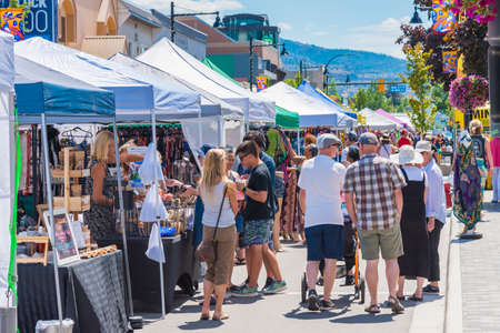 Penticton, British ColumbiaCanada - June 15, 2019: shoppers and sellers fill Main Street for the Penticton Community Market, a popular weekly event.