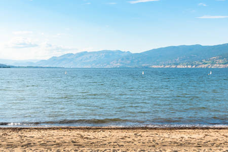 Sandy beach and lake with view of mountains and blue sky in summer Stock fotó