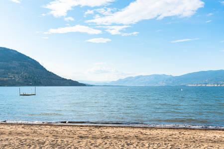 Summer evening view of sandy beach, lake, mountains, and blue sky at Okanagan Lake Stock fotó