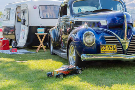 Penticton, British ColumbiaCanada - June 22, 2019: classic car and vintage camper trailer on display at the Beach City Peach Cruise, one of the largest car shows in North America.