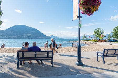 Penticton, British ColumbiaCanada - June 22, 2019: people sit on benches, walk along Lakeshore Drive and enjoy the beach on Okanagan Lake during the summer tourist season. 新聞圖片