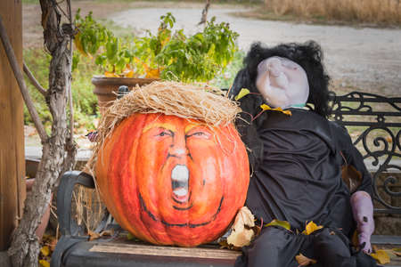 Penticton, British ColumbiaCanada - October  31, 2017: a humorous Halloween display on an outdoor bench, with a pumpkin decorated to look like U.S. President Donald Trump 新聞圖片