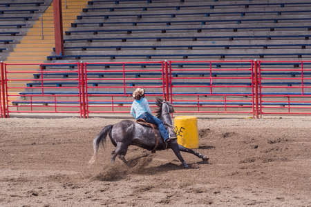 Williams Lake, British ColumbiaCanada - June 19, 2016: cowgirl cuts around barrel in barrel racing event called the Stampede Warm-Up to prepare for the Williams Lake Stampede, one of the largest stampedes in North America 新聞圖片