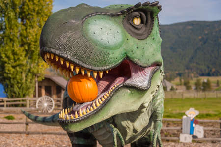 Armstrong, British ColumbiaCanada - October 23, 2016: Tyrannosaurus Rex statue holding pumpkin in its mouth, one of several dinosaur statues at the Log Barn, a popular tourist attraction