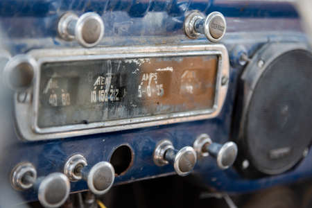 Dashboard at front of abandoned vintage truck with ammeter, oil indicator, various knobs