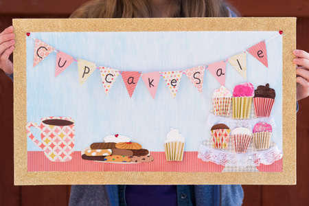 Girl holding up mixed media bake sale poster with cupcakes, cookies, and coffee cup Stock Photo