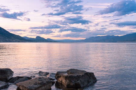 Sunset colours in cloudy sky reflecting in Okanagan Lake with view of mountains