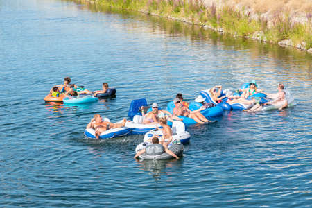 Penticton, British ColumbiaCanada - September 1, 2019: a group of friends float down the Penticton River Channel together on a hot day, a popular summer activity.