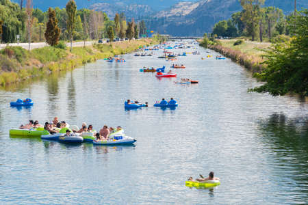 Penticton, British ColumbiaCanada - September 1, 2019: tourists and locals escape the summer heat with a relaxing float down the Penticton River Channel, a popular summer past-time. 新聞圖片
