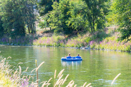 Man and woman float down Penticton River Channel on two-person inner-tube in summer 版權商用圖片
