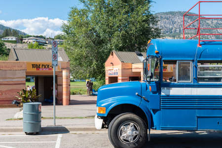 Penticton, British ColumbiaCanada - September 2, 2019: shuttle bus parked in front of Coyote Cruises River Float company, dropping off customers who floated down the Penticton River Channel. 新聞圖片